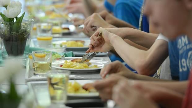 Mehrere Kinder sitzen beisammen und essen gemeinsam