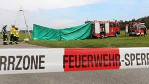 Feuerwehrleute haben auf dem Flugplatz einen Sichtschutz an der Unfallstelle errichtet. Am Morgen sind in Bad Saulgau zwei Fallschirmspringer bei einem Sprung tödlich verletzt worden, wie die Polizei mitteilte