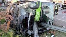 Sachsen, Leipzig: Einsatzkräfte der Feuerwehr stehen an der Unfallstelle neben dem verunglückten Bus auf der Autobahn 9