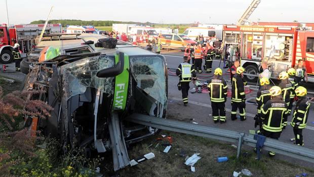 Einsatzkräfte der Feuerwehr stehen an der Unfallstelle auf der Autobahn 9 nahe Leipzig neben dem verunglückten Flixbus