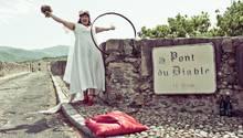 Rose trägt ein langes, weißes Hochzeitskleid, einen Schleier und Blumen. Um die Teufelsbrücke ein großer Ring befestigt.