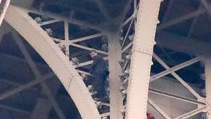 Ein Kletterer steht auf Eisenstreben hoch oben am Eifelturm