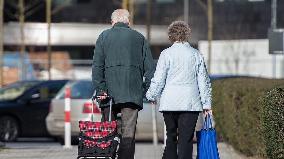 Ein älteres Ehepaar geht gemeinsam Hand in Hand