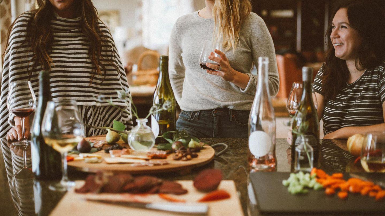 Frauen sitzen und stehen um Tisch und trinken Wein