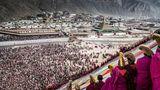 """China / Bildnis  Mönche des Labrang-Klosters entrollen zum tibetischen Neujahr einen 20 mal 30 Meter großen Teppich mit dem Antlitz Buddhas. Die eingerollte """"Thangka"""" wurde zuvor durch die Straßen des Klosterkomplexes getragen. Dabei rangeln Gläubige mit Wächtern, um die Stoffbahn einmal berühren zu können."""