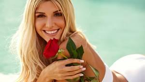 """Die neue """"Bachelorette"""" Gerda Lewis hält eine Rose in der Hand und liegt strahlend am Pool"""