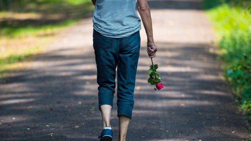 Eine Frau trägt eine rote Rose