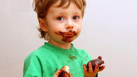 Eine schokoladenverschmierter Junge guckt traurig