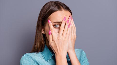 Eine Frau mit braunen Haaren hält sich die Hände vor die Augen und späht durch zwei Finger