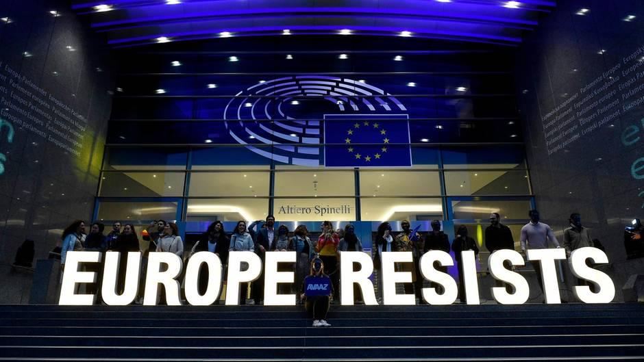 """Eine Aktivistengruppe hält die Worte """"Europe Resists"""" vor dem Europaparlament hoch"""
