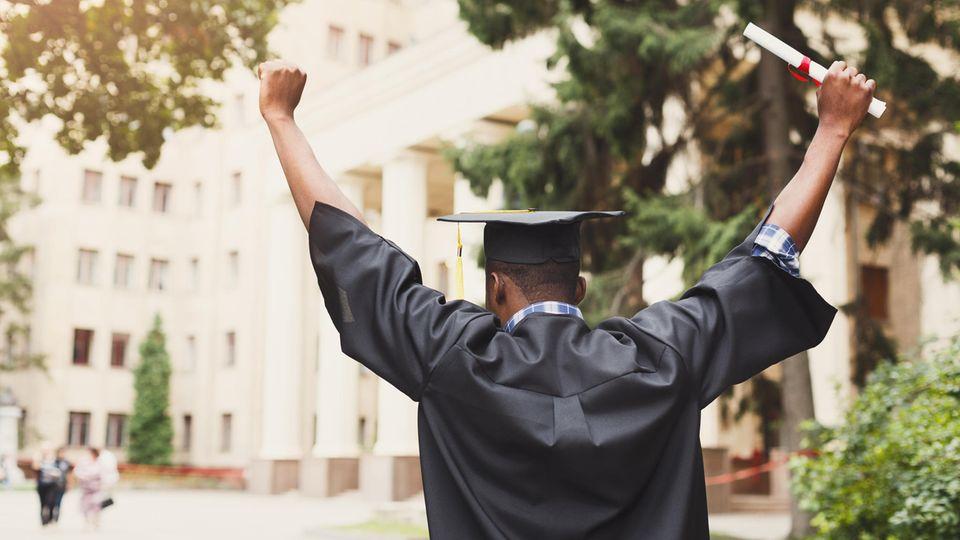 Ein junger, schwarzer Schüler von hinten. Er trägt eine Abschlussrobe, einen Uni-Abschluss-Hut und hält ein Diplom in der Hand
