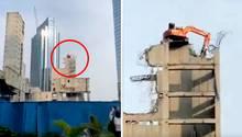 Ein Abrissbagger in Jakarta demontiertin luftiger Höhe das Hochhaus,auf demer steht.