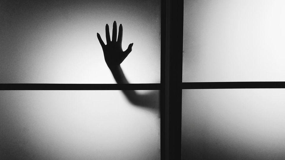 Hand hinter einer Glasscheibe