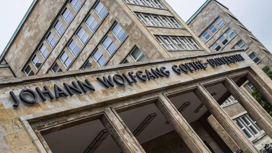"""Der Haupteingang des Campus Westend mit der Aufschrift """"Johann Wolfgang Goethe-Universität"""". Die Häuser sind aus hellem Stein."""
