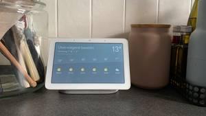 Ein Google Nest Hub auf einer Arbeitsfläche einer Küche. Auf dem Bildschirm sieht man die Wetteranzeige.