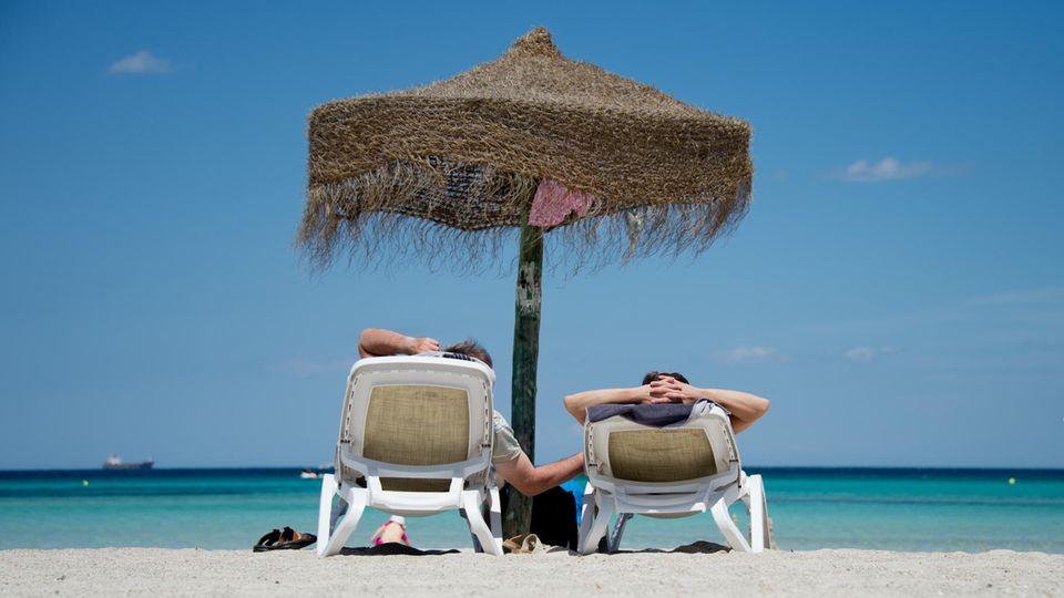 Zwei Urlauber liegen am Strand unter einem Sonnenschirm