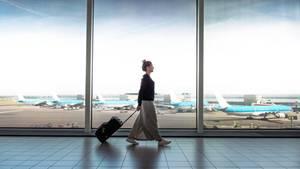 Frau geht mit einem Rollkoffer durch eine Flughafenhalle