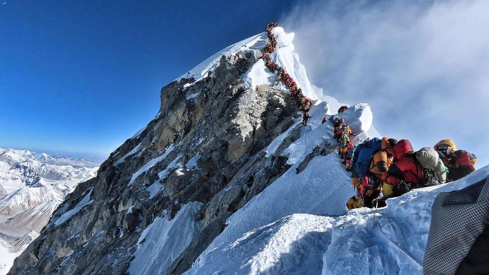 Hochsaison im Himalaya: Dicht an dicht reihen sich die Alpinisten am Gipfelgrat des Mount Everest. Schon bald gibt es Gegenverkehr durch absteigende und umkehrende Kletterer.