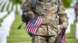 US-Soldat geht am Memorial Day über einen Soldatenfriedhof