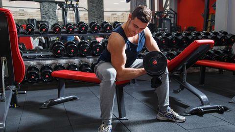 Mann sitzt mit Hantel in einem Fitnessstudio.