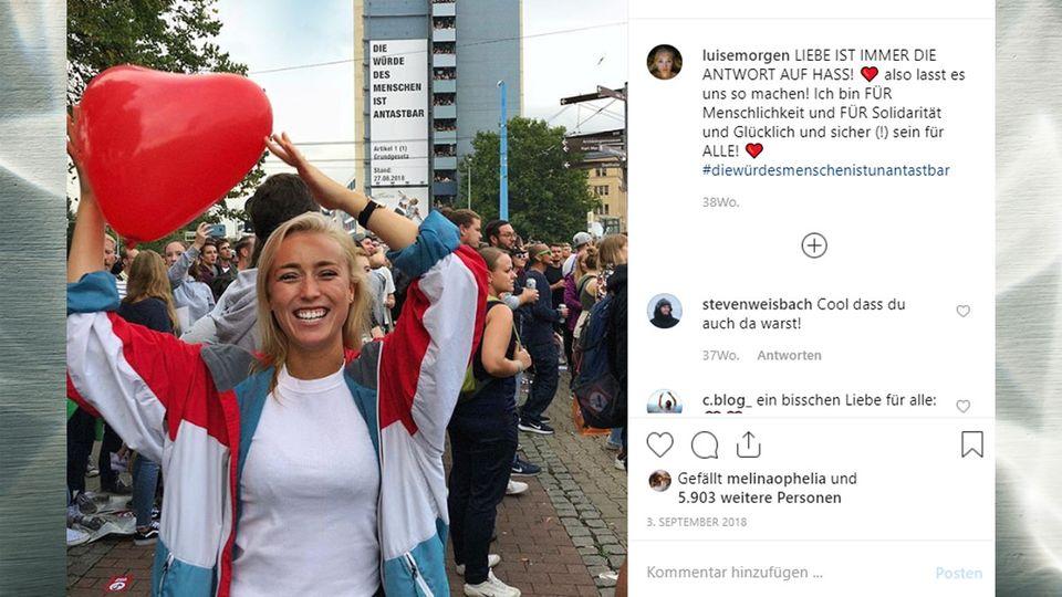 Blondes Mädchen in einer Menschenmenge mit einem herzförmigen Luftballon in der Hand.