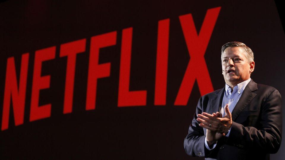 Ted Sarandos hält eine Präsentation in Rom. Hinter ihm prangt rot auf schwarz das der Netflix-Schriftzug.