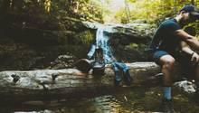Ein Mann sitzt auf Baumstamm mit Wanderschuhen