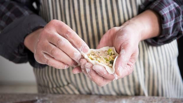 Dumplings in der Hand halten und mit Hackfleisch füllen
