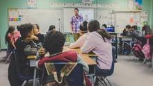 Kinder, die in einem Klassenzimmer sitzen. Sie schauen einen Lehrer an.