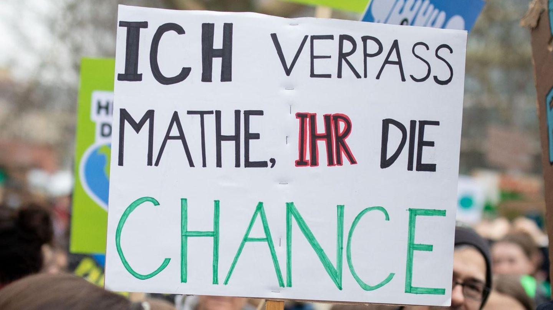 """Demonstranten halten ein Schild hoch: """"Ich verpass' Mathe, ihr die Chance""""."""