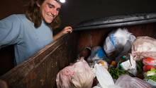 Mann freut sich über Lebensmittel beim sogenannten Containern
