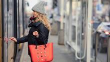 Frau steht an Straßenbahnhaltestelle. Im Hintergrund spiegelt sich ein Pkw.