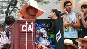 Ein Demonstrant der EcoWaste-Bewegung auf den Philippinen trägt einen selbstgebastelten, mit Plastik gefüllten Container.