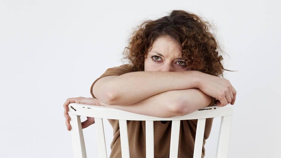 Traurige, junge Frau auf einem Stuhl