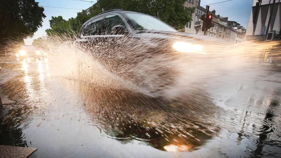 Aus einer Pfütze spritzt Wasser hoch, als ein Auto durchfährt