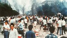 Rauchsäulen, Verwüstung und ratlose Menschen auf der Changan Avenue nahe dem Tian'anmen in Peking am 4. Juni 1989