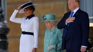 Die Hand gehört eigentlich nicht an den Hut: Melania Trump (l.) muss bei einem Windstoß nach oben greifen. Der Hut der Queen sitzt hingegen perfekt. Donald Trump bleibt unbeirrt.