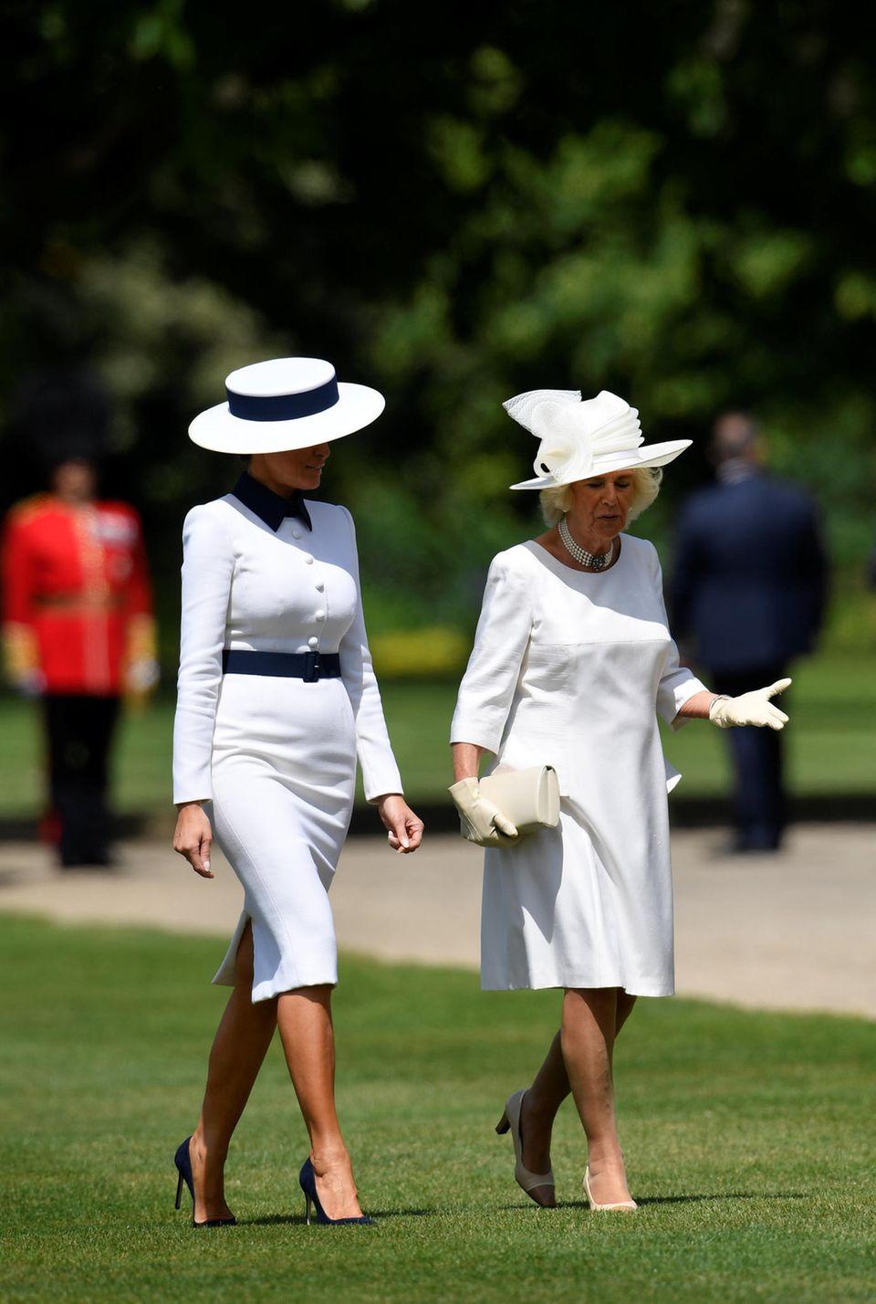 Ganz in Weiß: Herzogin Camilla (r.) plauscht mit Melania Trump. Die High Heels sind offenbar auch auf Rasen kein Problem.