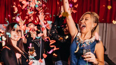 Frauen feiern mit Sektglas in der Hand und fliegenden Konfetti.