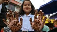 Ein muslimisches Mädchen zeigt ihre Hände, die sie zum Eid-Fest – dem Ende des Fastenmonats Ramadan – mit Hennadekoriert hat.
