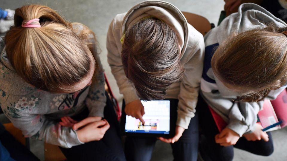 Drei Mädchen werden von oben fotografiert, sie schauen YouTube auf einem Tablet