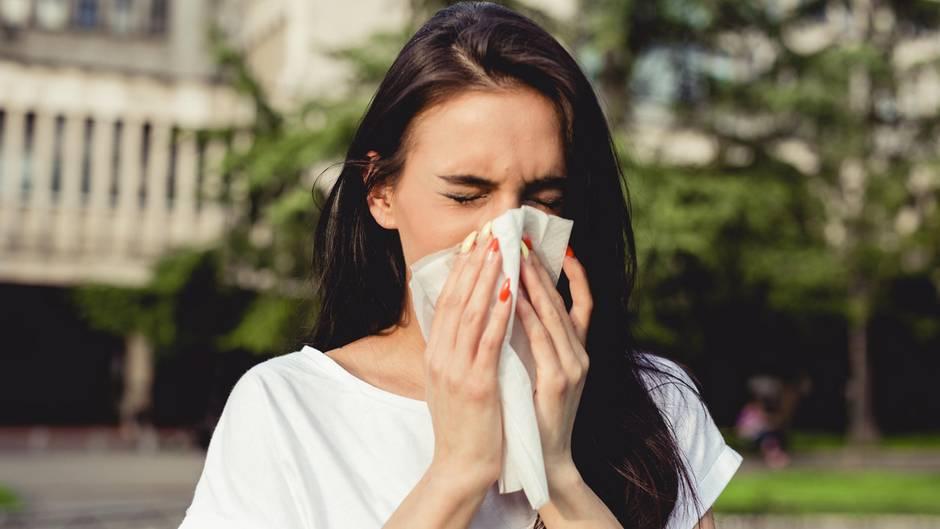 Sommergrippe: Eine Frau benutzt ein Taschentuch