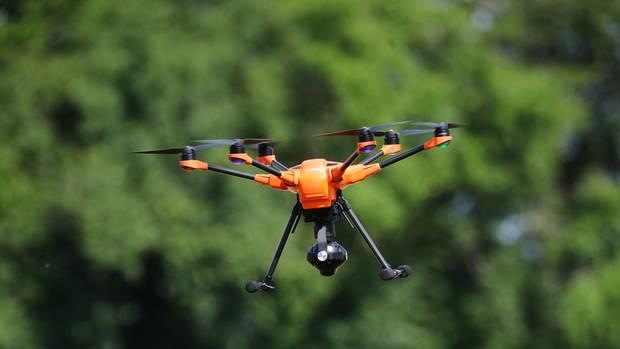 Eine orangene Drohne mit Wärmebildkamera an der Unterseite fliegt über ein Feld