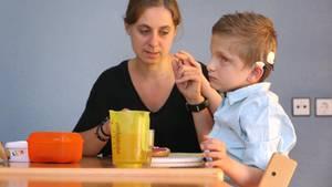 Erzieherin Stefanie Tröster sitzt in einer Wohngruppe des Blindeninstitutes mit dem taubblinden Lucas beim Frühstück