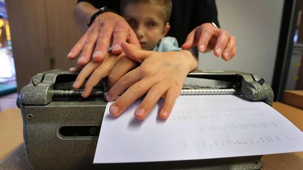 Der taubblinde Lucas ertastet, unterstützt von seiner Erzieherin Stefanie Tröster, Buchstaben in Blindenschrift