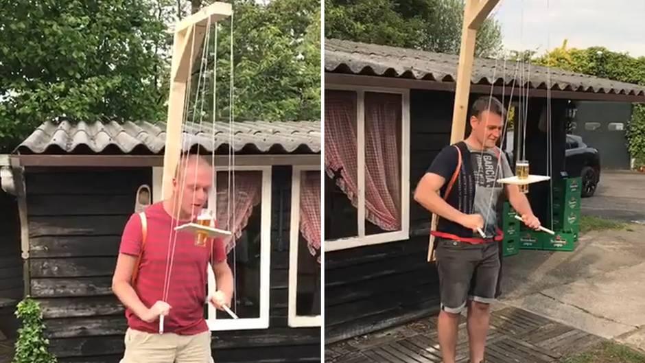 Mit Hilfe eines marionettenartigen Gestells müssen Männer ein Bierglas auf einem Holzbrett zum Mund balancieren.
