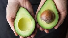 Avocadokern mitessen: Ein Mann hält eine aufgeschnittene Avocado in der Hand