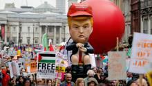 Am Trafalgar Square haben Demonstrantendiesen knapp fünf Meter großen sprechenden Donald-Trump-Roboter aufgebaut, der mit heruntergelassener Hose auf einer Goldtoilette sitzt