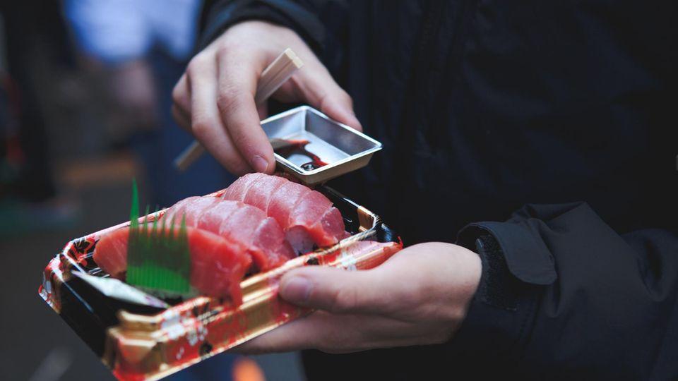 Mann mit einer Sushi Packung in der Hand