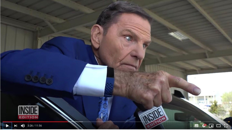 Kenneth Copeland steht in blauem Anzug vor seiner Autotür. Er zeigt mit dem Finger auf die Reporterin und schaut aggressiv.